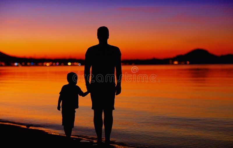 Fadern och sonen nära vattnet kantar på solnedgången fotografering för bildbyråer