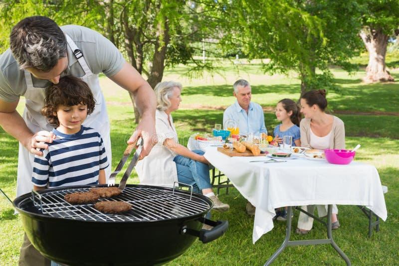 Fadern och sonen på grillfestgallret med familjen som har lunch parkerar in royaltyfria bilder