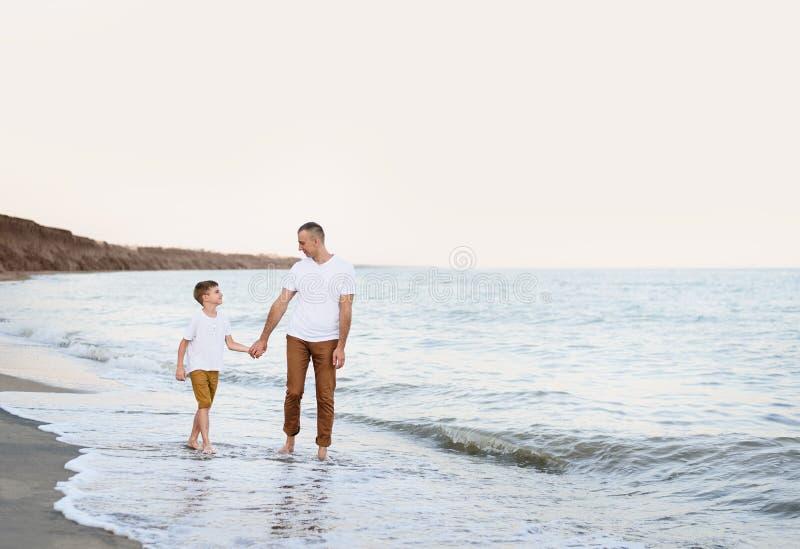 Fadern och sonen passerar handen längs semestern för familjen för havskusten kamratskap royaltyfri foto