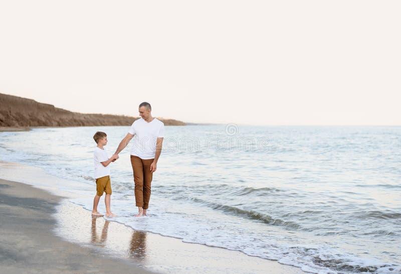 Fadern och sonen passerar handen längs semestern för familjen för havskusten kamratskap royaltyfri bild