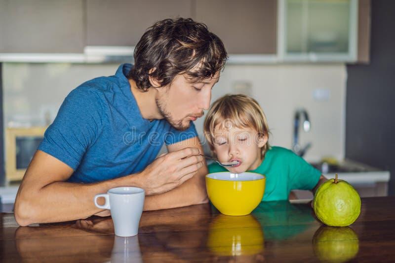 Fadern och sonen ?r tala och le, medan ha en frukost i k?k fotografering för bildbyråer