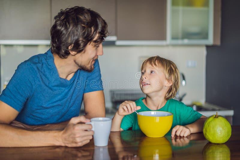 Fadern och sonen ?r tala och le, medan ha en frukost i k?k arkivbilder