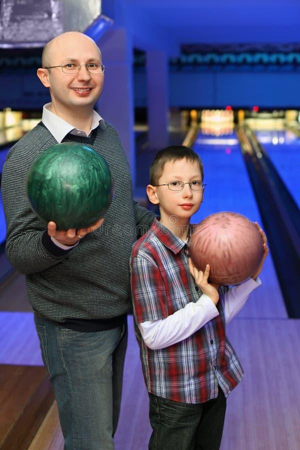 Fadern och sonen rymmer bollar för bowling arkivfoto