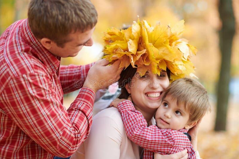 Fadern och sonen satte gula stupade sidor på moderhuvudet Den lyckliga familjen är i höststad parkerar Barn och föräldrar Dem som royaltyfria foton