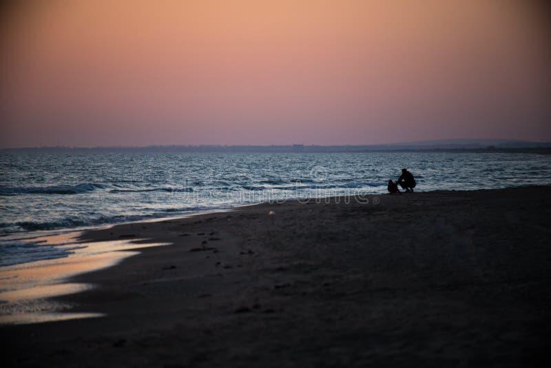 Fadern och sonen sitter nära havet på solnedgången royaltyfri fotografi