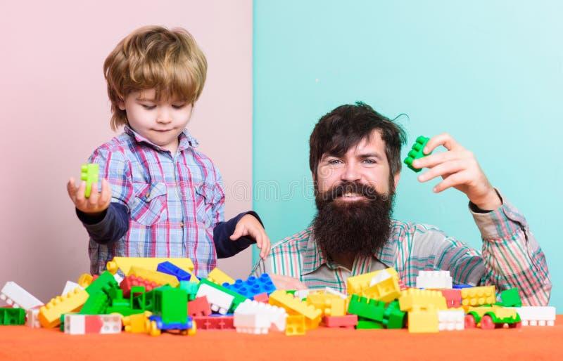 Fadern och sonen skapar f?rgrika konstruktioner med tegelstenar Barnav?rdutveckling och uppfostran Skäggig fader och pojke arkivbild