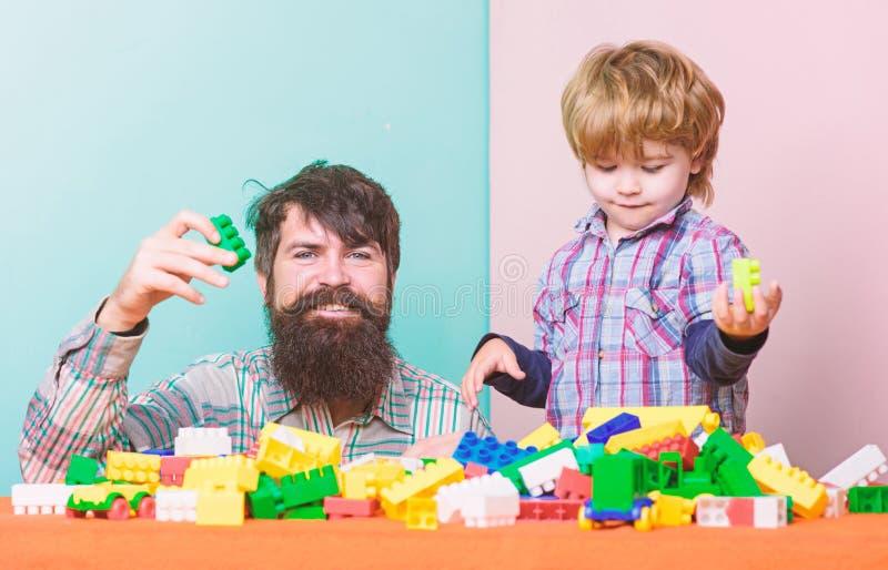 Fadern och sonen skapar f?rgrika konstruktioner med tegelstenar Barnav?rdutveckling och uppfostran Sk?ggig fader och pojke royaltyfri bild