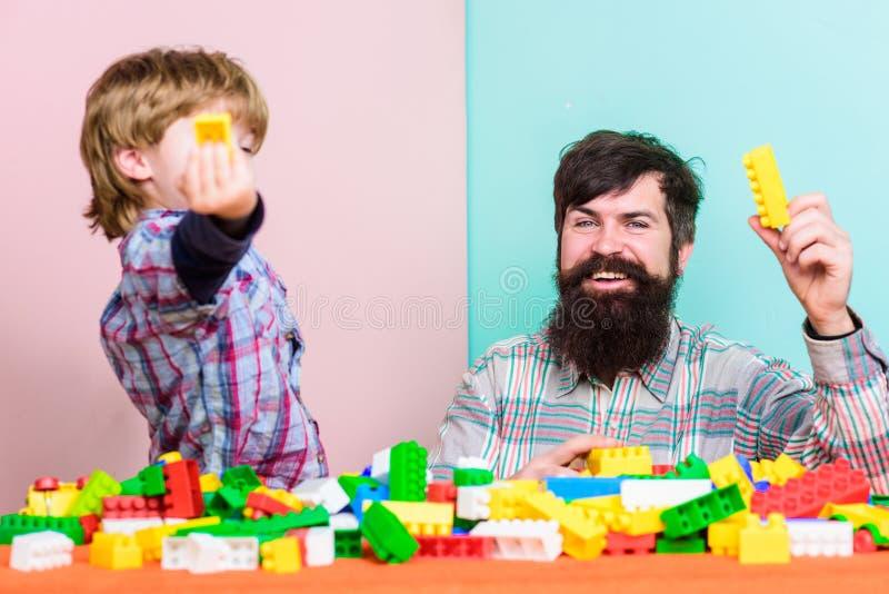 Fadern och sonen skapar konstruktioner Sk?ggig man- och sonlek tillsammans Varje farsa och son m?ste g?ra tillsammans Farsa och u arkivbild