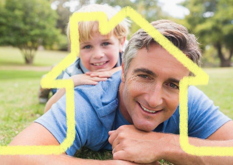 Fadern och sonen som överdras med huset, formar att ligga in parkerar royaltyfria foton