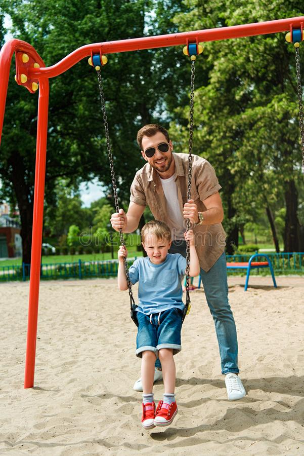 fadern och sonen som har gyckel på gunga på lekplatsen i, parkerar och att se royaltyfri fotografi