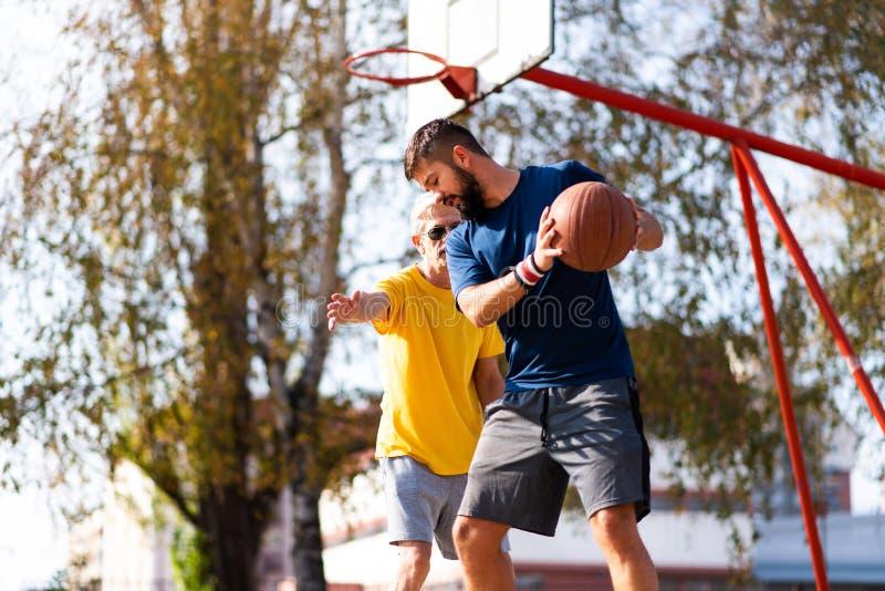 Fadern och sonen som spelar basket i, parkerar fotografering för bildbyråer