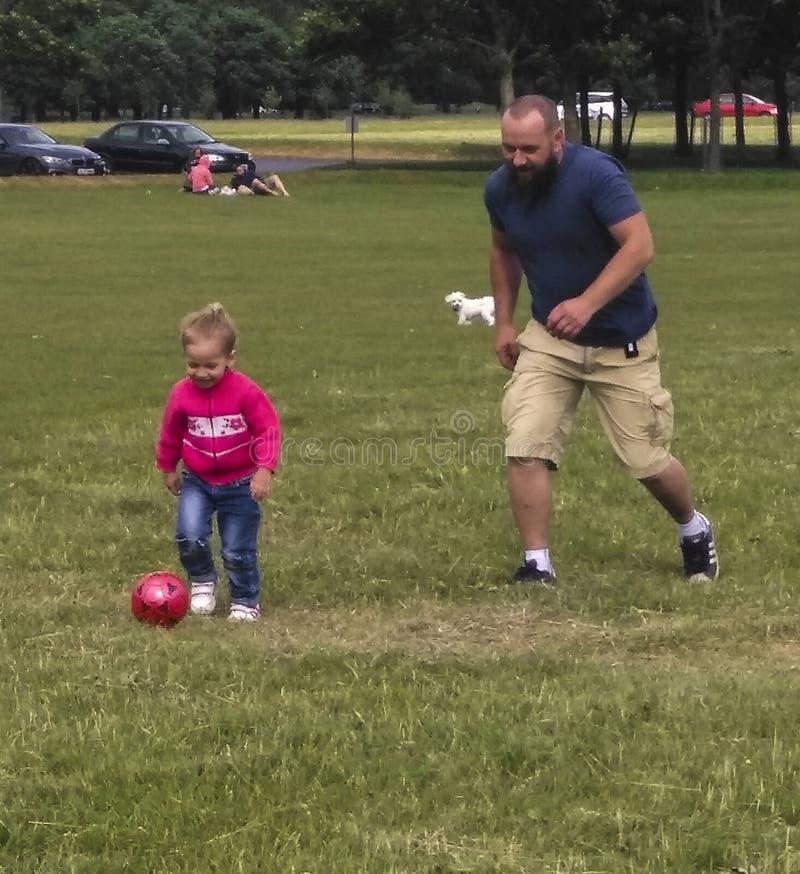 Fadern och sonen som spelar fotboll i phoenix, parkerar, Republiken Irland arkivfoton