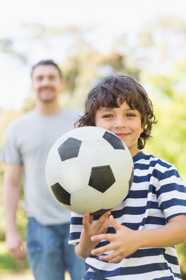 Fadern och sonen som spelar fotboll parkerar in arkivbild