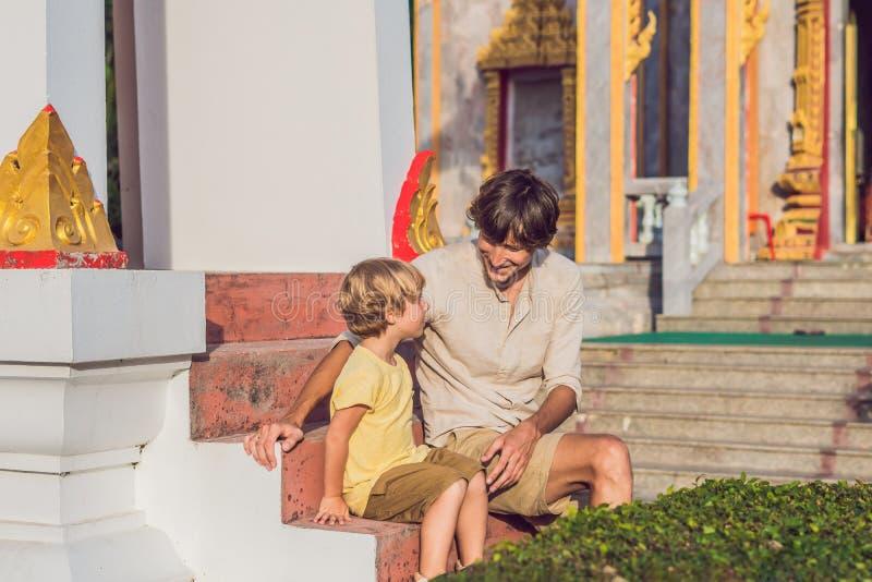 Fadern och sonen som turister ser Wat Chalong, är det mest importan royaltyfri bild