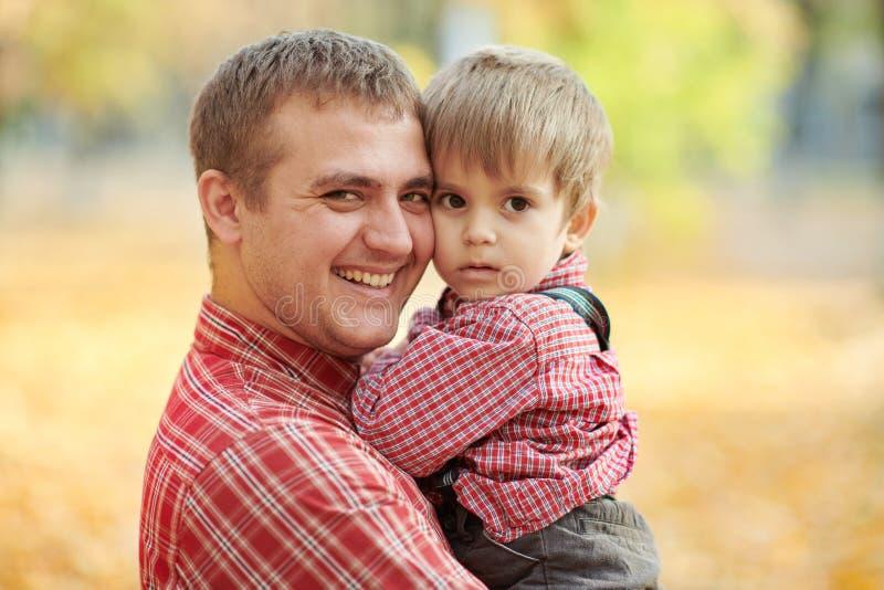 Fadern och sonen spelar, och ha gyckel i höststad parkera Dem som poserar, le som spelar Ljusa gula träd royaltyfri fotografi