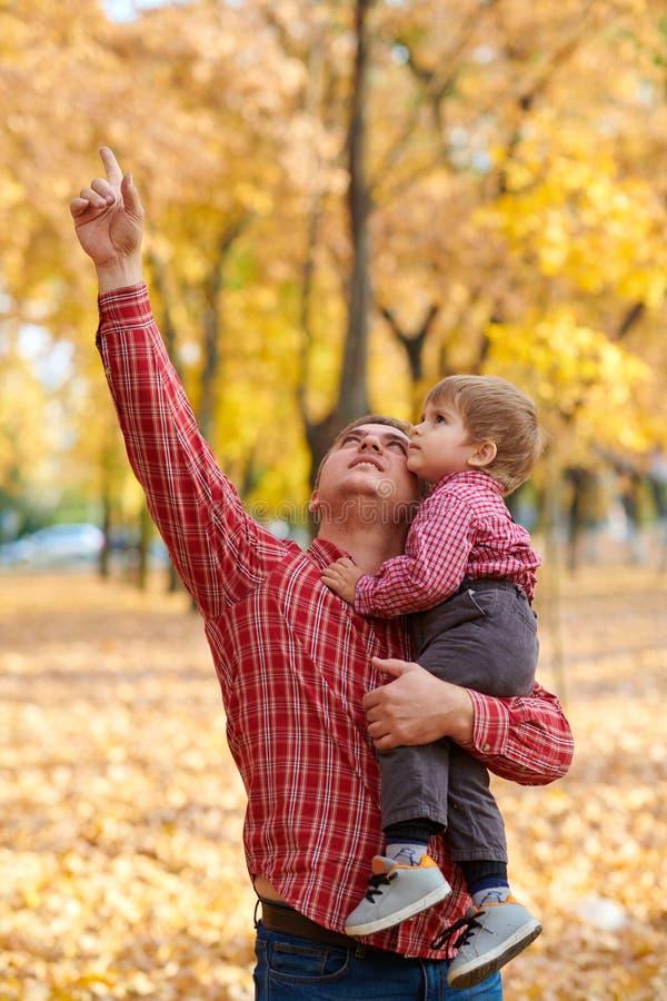 Fadern och sonen spelar, och ha gyckel i höststad parkera Dem som poserar, le som spelar Ljusa gula träd royaltyfri foto
