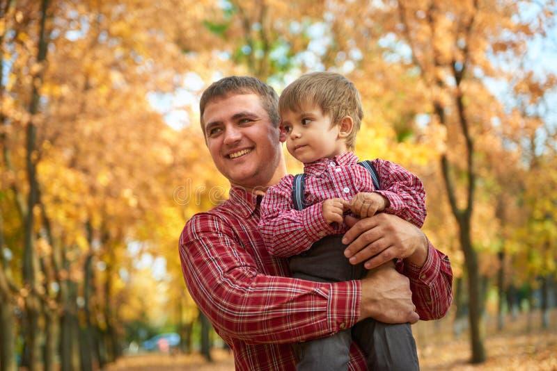 Fadern och sonen spelar, och ha gyckel i höststad parkera Dem som poserar, le som spelar Ljusa gula träd royaltyfria bilder