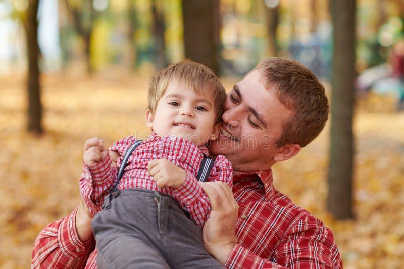 Fadern och sonen spelar, och ha gyckel i höststad parkera Dem som poserar, le som spelar Ljusa gula träd arkivfoto