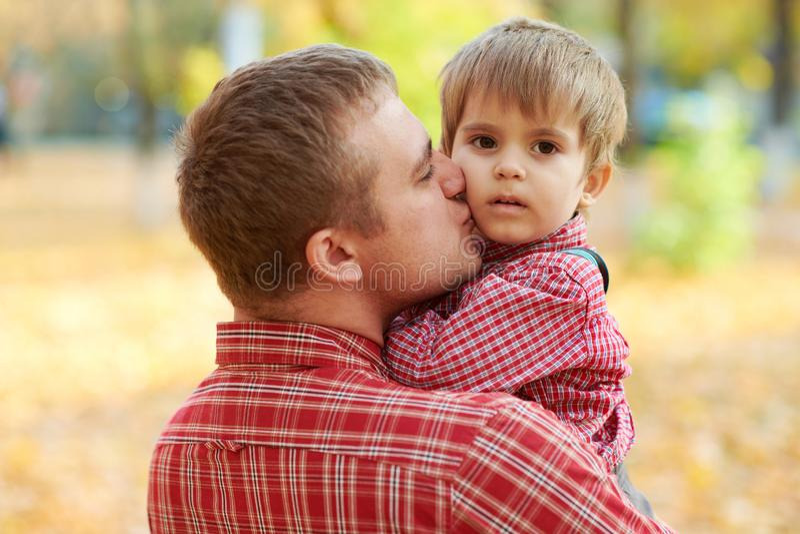 Fadern och sonen spelar, och ha gyckel i höststad parkera Dem som poserar, le som spelar Ljusa gula träd arkivbild