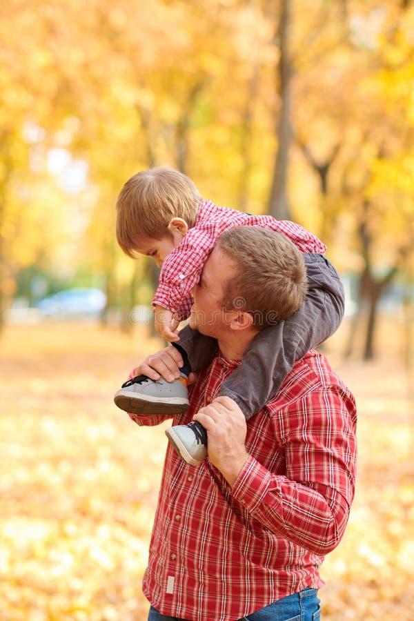 Fadern och sonen spelar, och ha gyckel i höststad parkera Dem som poserar, le som spelar Ljusa gula träd arkivbilder