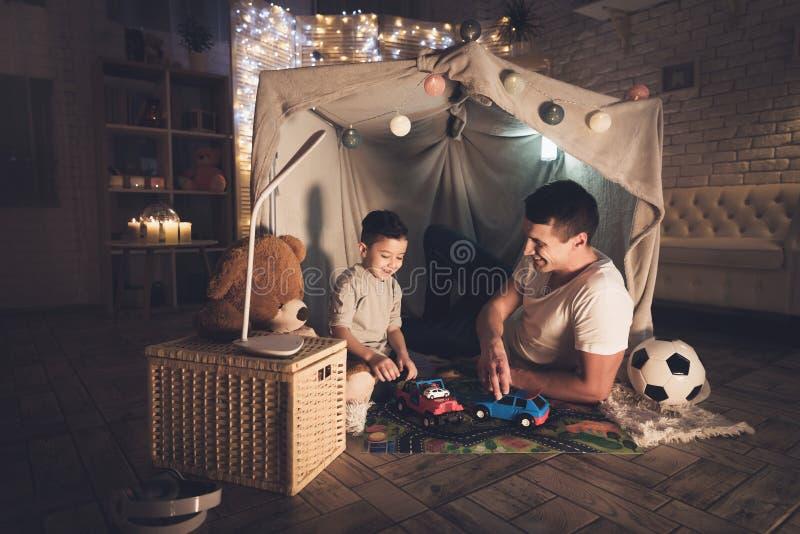 Fadern och sonen spelar med leksakbilar på mattvägen på natten hemma arkivbilder