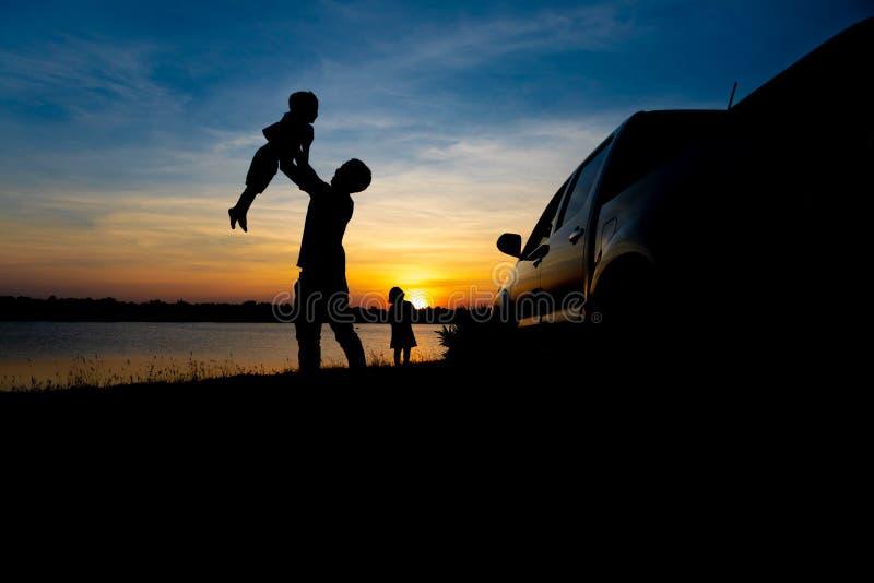 Fadern och sonen spelar på sjön på solnedgången Folket har gyckel på fältet royaltyfri bild