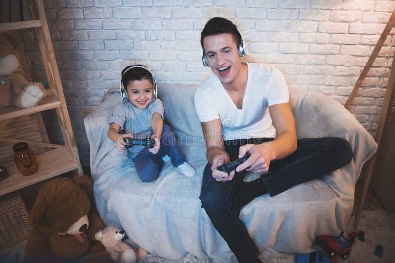 Fadern och sonen spelar videospel på tv på natten hemma arkivbild
