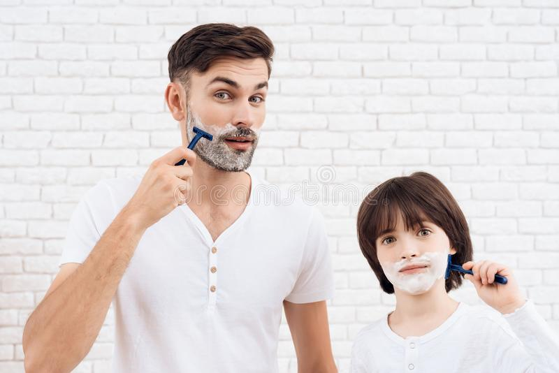 Fadern och sonen spenderar tid tillsammans Farsa och son i den samma kläderna Den lilla mörker-haired pojken lär att raka arkivbild