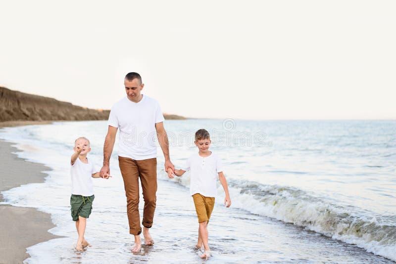 Fadern och två söner promenerar kusten Tycka om semester royaltyfri fotografi