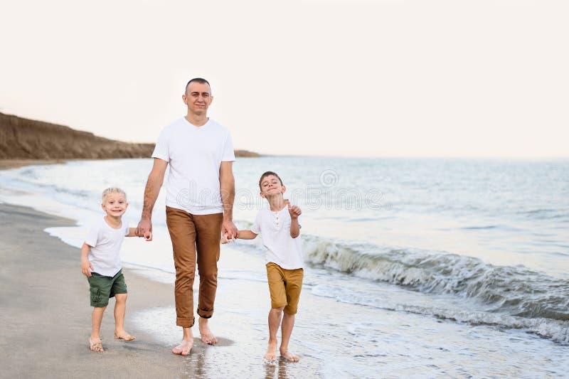 Fadern och två söner promenerar kusten Tycka om semester royaltyfri foto