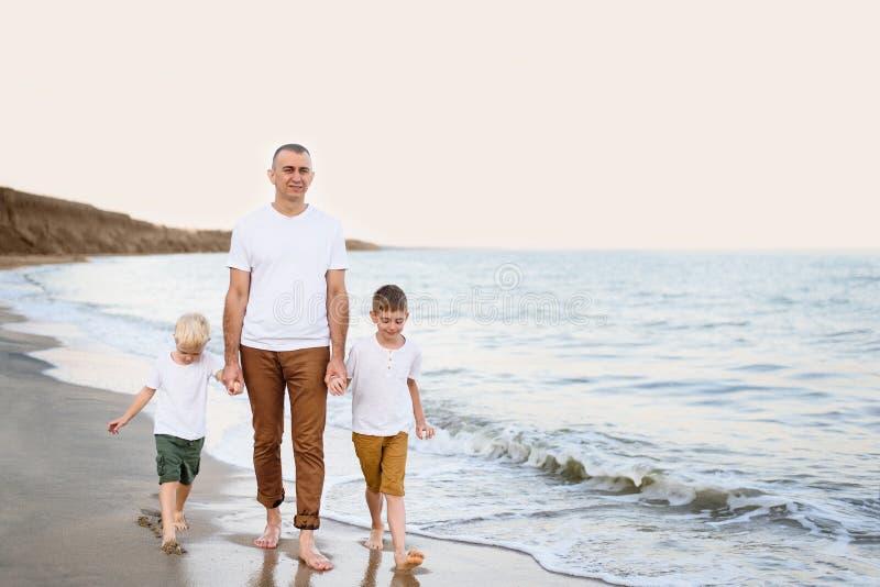 Fadern och två söner promenerar kusten Tycka om semester arkivbild