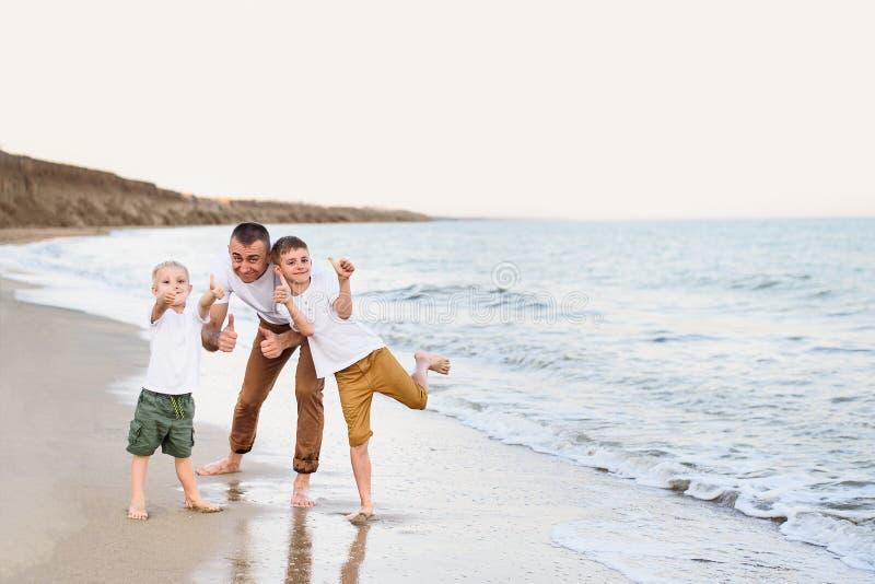 Fadern och två söner visar grupp, havskust som tycker om semester arkivfoto