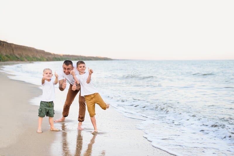 Fadern och två söner visar grupp, havskust som tycker om semester arkivbild
