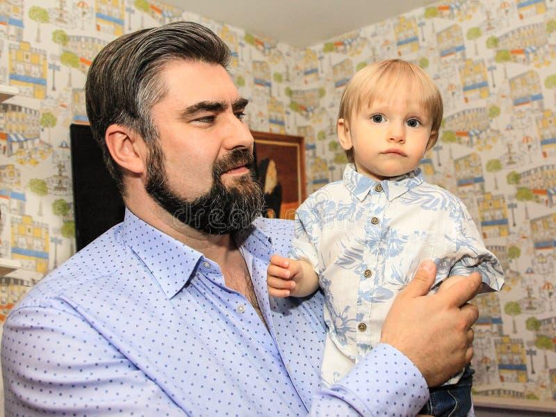 Fadern rymmer dengamla sonen i hans armar Begrepp av faderlig förälskelse royaltyfria bilder