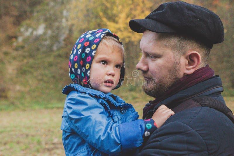 Fadern rymmer dottern förestående, medan hon gråter arkivbilder