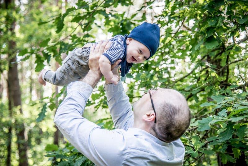 Fadern rymmer hans behandla som ett barn upp i luften i skog royaltyfria bilder