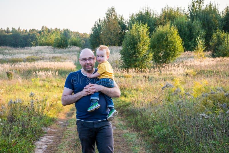 Fadern rymmer hans litet barn royaltyfria bilder