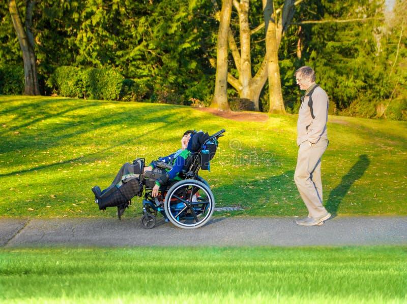 Fadern som går med den rörelsehindrade sonen i rullstol på sjön, parkerar royaltyfria foton