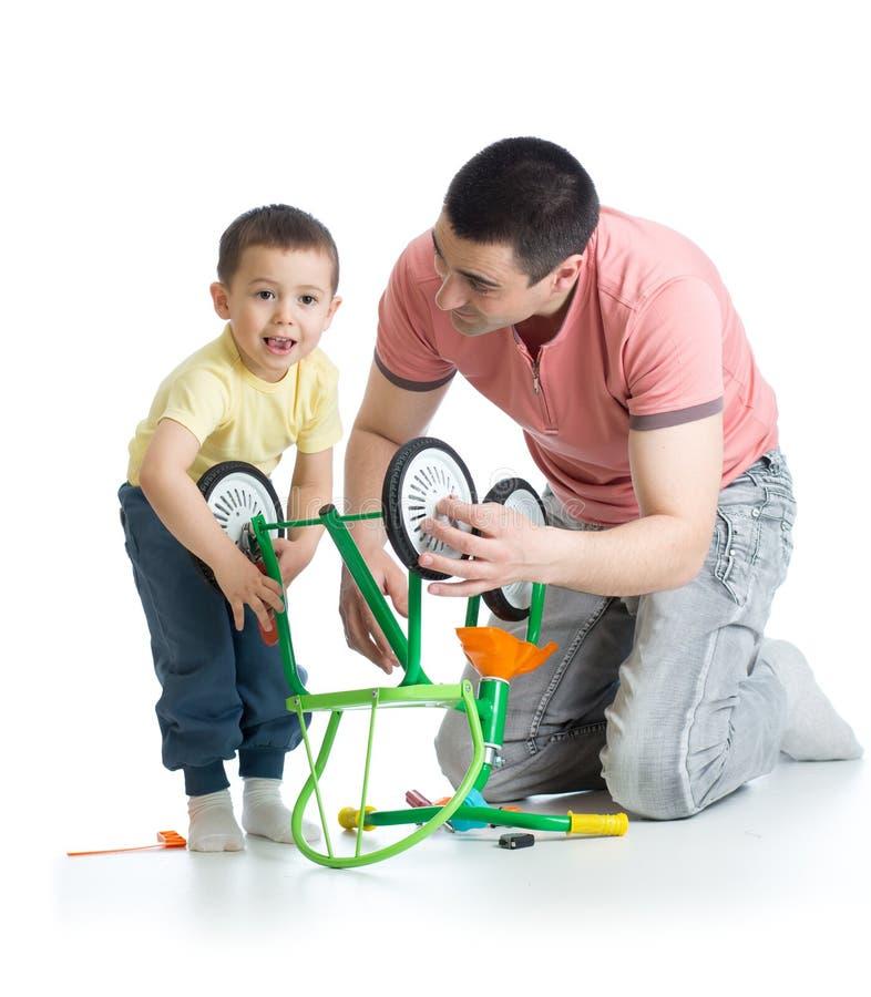 Fadern som reparerar barn, cyklar med hans barnson fotografering för bildbyråer