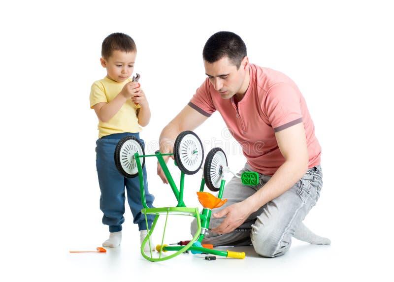 Fadern som reparerar barn, cyklar med hans son som isoleras arkivfoto