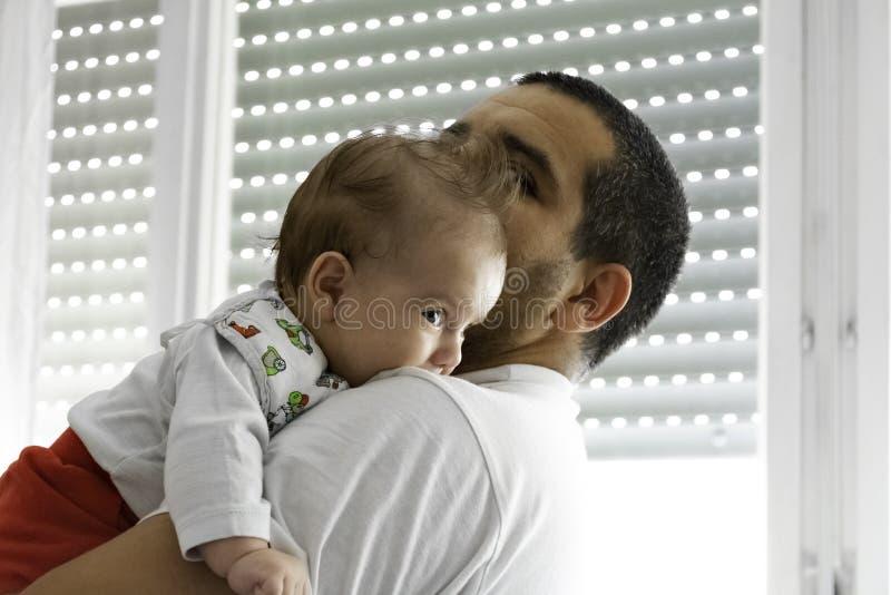Fadern som rymmer bärande sjukvård som kysser barnuppfostran som tar omsorg av, behandla som ett barn ståenden för det nyfödda ba royaltyfri bild