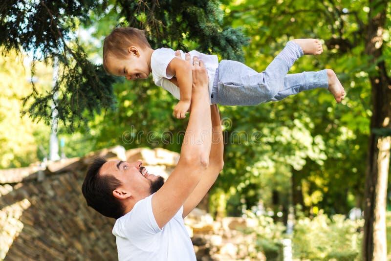 Fadern som spelar med den lilla sonen, lyfter och håller honom ovanför huvudet på en picknick i, parkerar Både farsan och barnet  royaltyfri foto