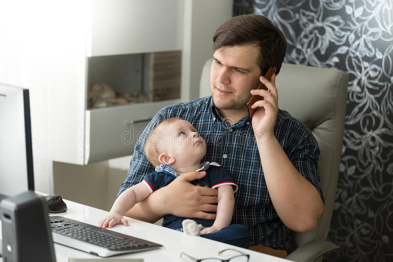 Fadern som talar vid telefonen och tar omsorg av hans, behandla som ett barn arkivfoto