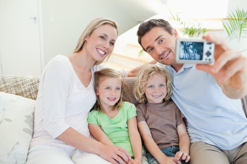 Fadern som tar familjen, föreställer på sofaen royaltyfri bild