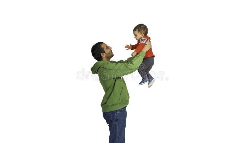 Fadern som upp rymmer och lyfter hans gulligt, behandla som ett barn royaltyfri foto