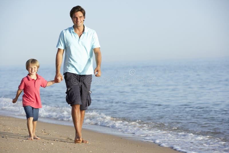 Fadern And Son Enjoying promenerar stranden royaltyfria bilder