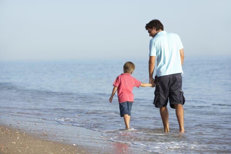 Fadern And Son Enjoying promenerar stranden royaltyfri foto