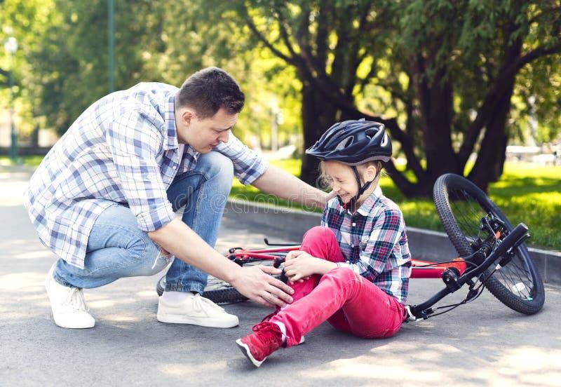 Fadern tröstar hans flicka, når han har fallit från cykeln arkivfoton
