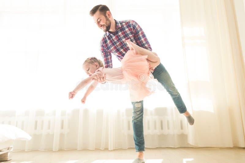Fadern undervisar f?r att dansa hans gulliga lilla dotter royaltyfri foto