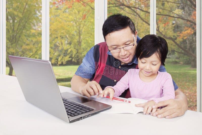 Fadern undervisar hans barn som gör läxa med boken royaltyfri fotografi